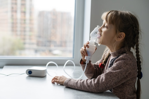 Petite fille faisant l'inhalation avec nébuliseur à la maison enfant nébuliseur d'inhalateur d'asthme