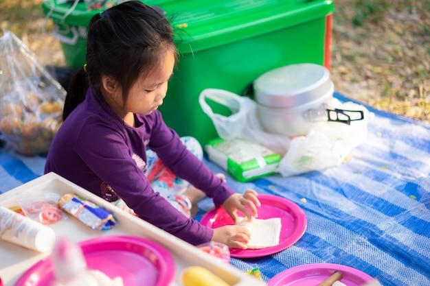 Petite fille faisant le petit déjeuner entre camping