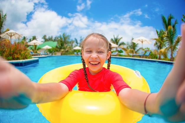 Petite fille faisant selfie à l'anneau de caoutchouc gonflable s'amuser dans la piscine