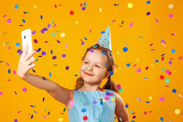 Petite fille faisant selfie sous tomber de confettis.