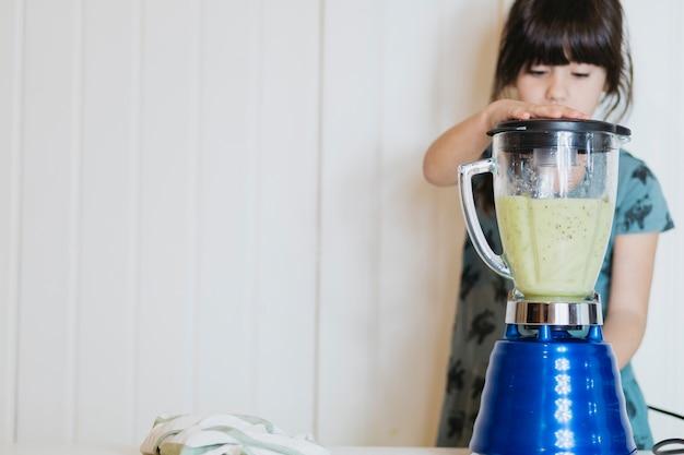 Petite fille faisant un smoothie avec un mélangeur