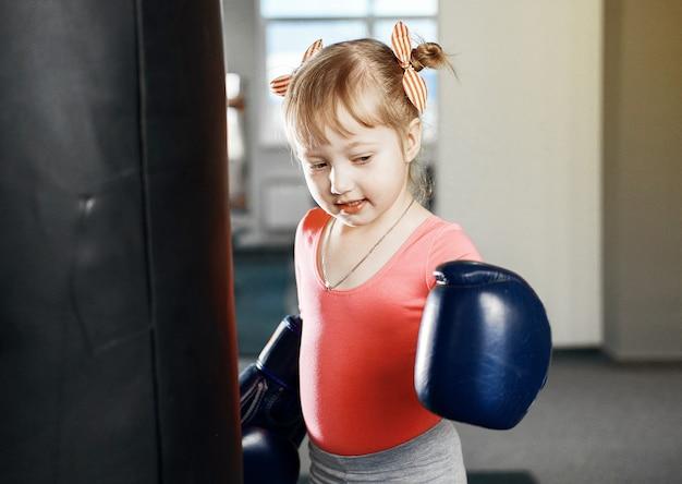 La petite fille fait de la boxe, petite fille avec de gros gants pour adultes boxe, grands gants de boxe bleus sur ses mains d'une petite fille, une petite fille entre dans un sac de boxe
