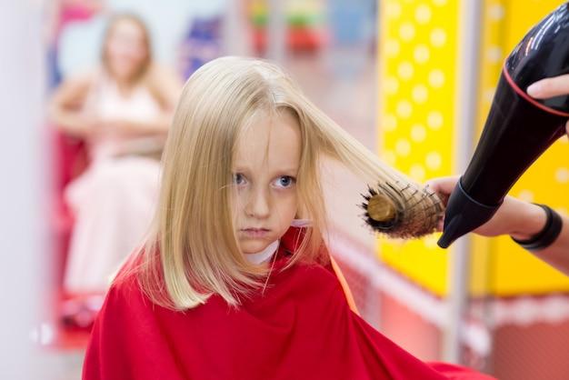 Une petite fille fait une coupe de cheveux chez le coiffeur.