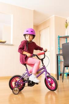 Petite fille fait du vélo dans son salon