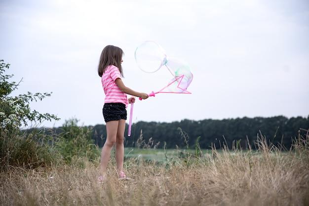 Petite fille fait de grosses bulles de savon multicolores sur la nature sur le terrain