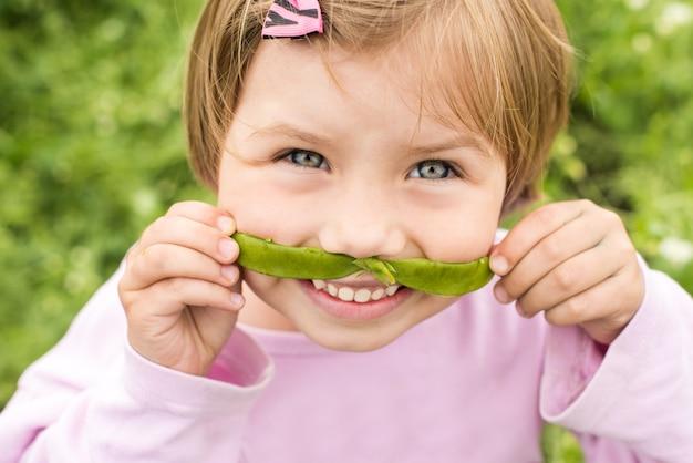 Petite fille fait une moustache de la cosse de pois