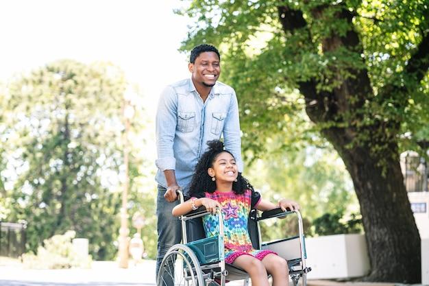 Une petite fille en fauteuil roulant appréciant et s'amusant avec son père lors d'une promenade ensemble à l'extérieur