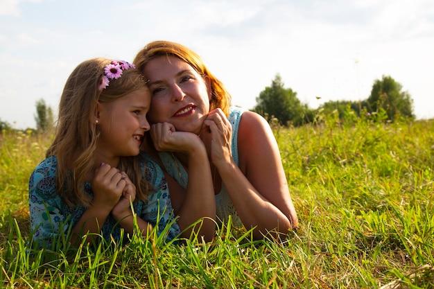 Une petite fille et une femme-mère sont allongées sur l'herbe verte dans un champ, un temps d'été ensoleillé, le sourire et la joie d'un enfant, une fille raconte les secrets de ses enfants