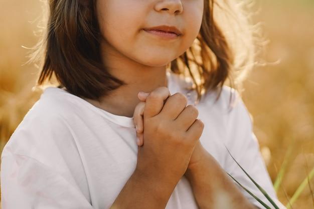 Petite fille ferma les yeux, priant dans un champ de blé. les mains jointes en prière. concept de religion