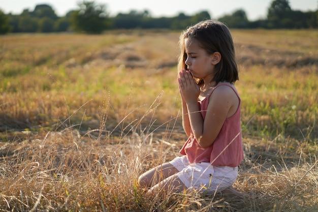 La petite fille ferma les yeux, priant dans un champ.
