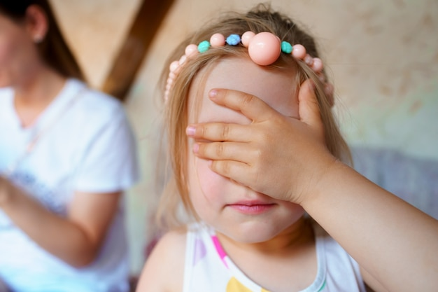 Petite fille fermant les yeux, je ne veux pas regarder la caméra