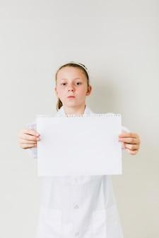 Petite fille ferme tenant une feuille de papier blanc