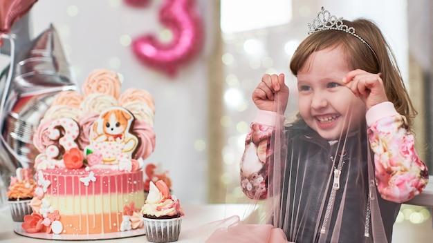 Petite fille à la fête d'anniversaire en regardant avec bonheur