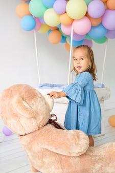 Une petite fille fête son anniversaire. gros ours en peluche dans un cadeau d'anniversaire.