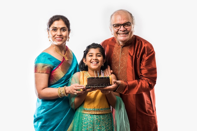 Petite fille ou fille asiatique indienne mignonne célébrant l'anniversaire avec les grands-parents tout en portant des vêtements ethniques