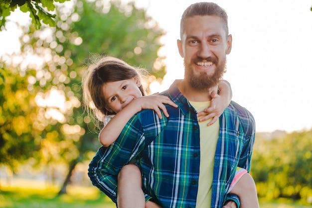 Petite fille fille enfant tenant la main de son père dans la nature au coucher du soleil.
