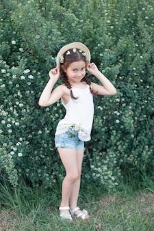 Une petite fille avec des fleurs blanches dans les mains et les cheveux, regarde la caméra et sourit.