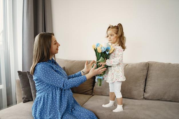 Petite fille avec des fleurs. maman est enceinte. salutations à maman.