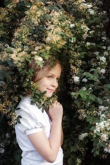 Petite fille avec des fleurs, portrait près de buisson en fleurs, gros plan. le printemps. concept de printemps.