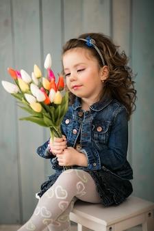 Petite fille avec des fleurs en studio