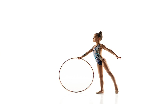 Petite fille flexible isolée sur blanc. petit modèle féminin en tant qu'artiste de gymnastique rythmique en justaucorps brillant. g