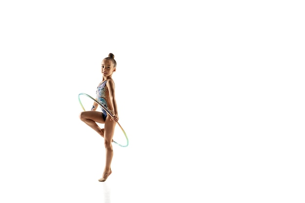 Petite fille flexible isolée sur blanc. petit modèle féminin en tant qu'artiste de gymnastique rythmique en justaucorps brillant.