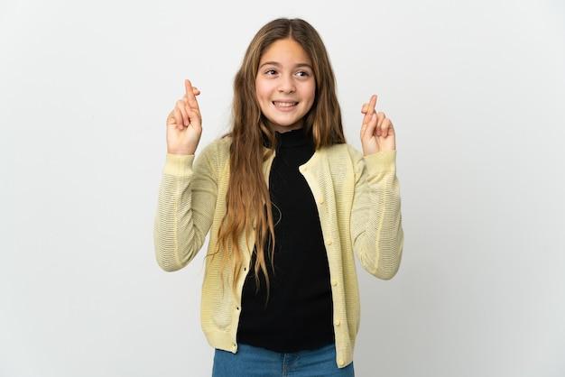 Petite fille sur fond blanc isolé avec les doigts croisés et souhaitant le meilleur