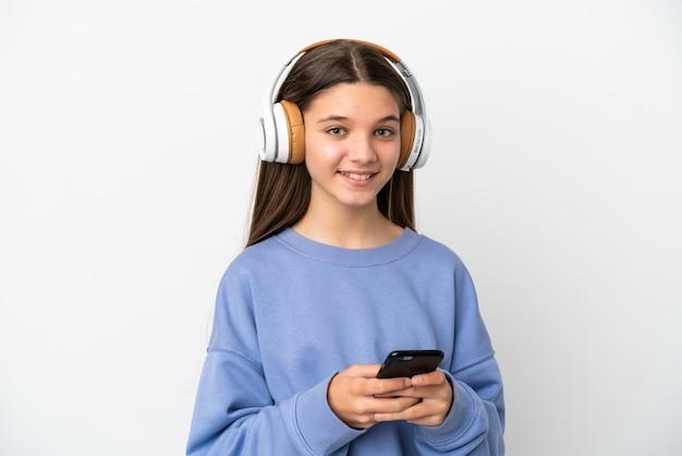Petite fille sur fond blanc isolé, écouter de la musique avec un mobile et à l'avant