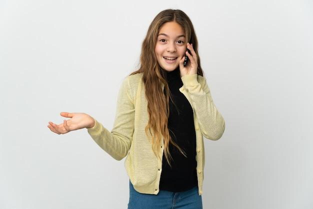 Petite fille sur fond blanc isolé gardant une conversation avec le téléphone portable avec quelqu'un