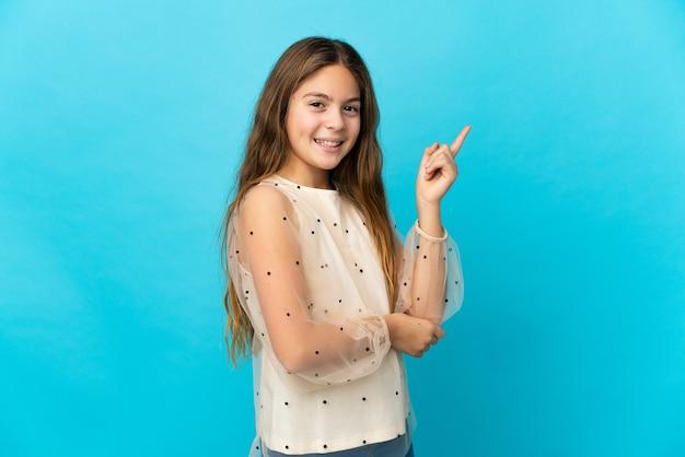 Petite fille sur fond bleu isolé heureux et pointant vers le haut