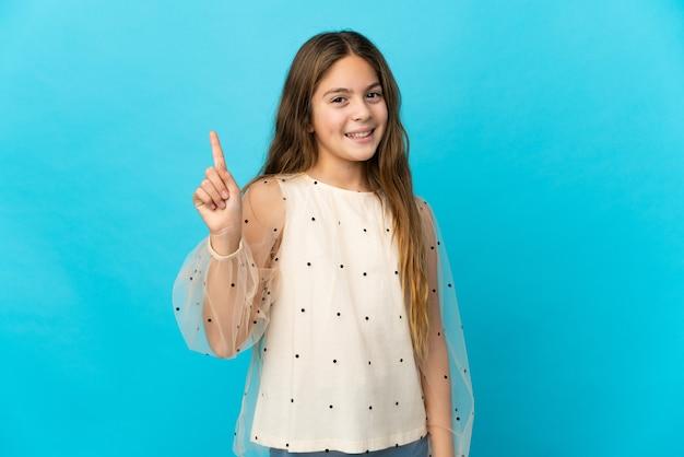 Petite fille sur fond bleu isolé montrant et soulevant un doigt en signe du meilleur