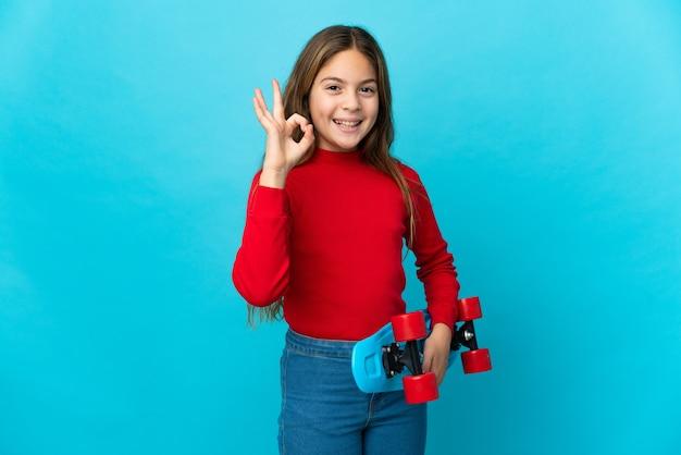 Petite fille sur fond bleu isolé avec un patin et faisant signe ok
