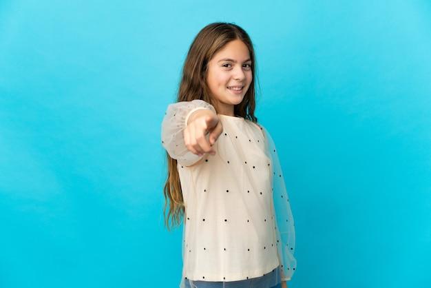 Petite fille sur fond bleu isolé pointant vers l'avant avec une expression heureuse