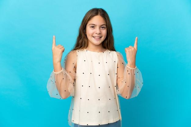 Petite fille sur fond bleu isolé pointant vers une excellente idée