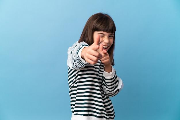 Petite fille sur fond isolé pointant vers l'avant et souriant