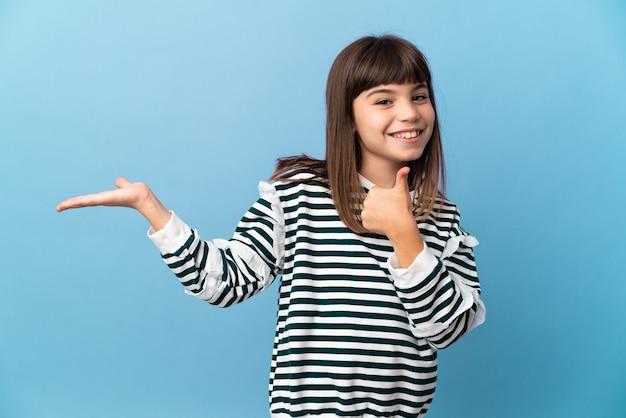 Petite fille sur fond isolé tenant copyspace imaginaire sur la paume pour insérer une annonce et avec les pouces vers le haut