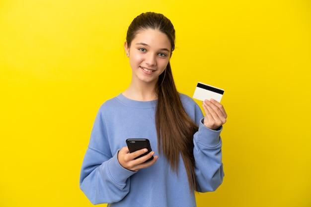 Petite fille sur fond jaune isolé achetant avec le mobile avec une carte de crédit