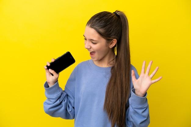 Petite fille sur fond jaune isolé utilisant un téléphone portable et chantant