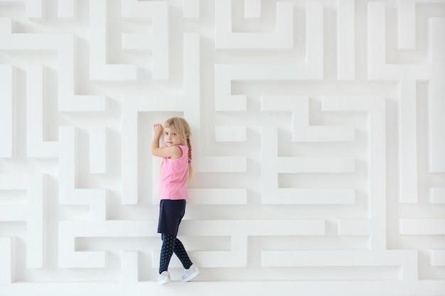 Petite fille sur fond de mur de labyrinthe