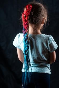 Petite fille sur fond noir avec des bandes élastiques afro turquoise et rose, des nattes attachées en queue de cheval