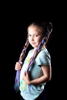 Une petite fille sur fond noir avec des nattes de bandes élastiques afro violettes sur une bande élastique no...