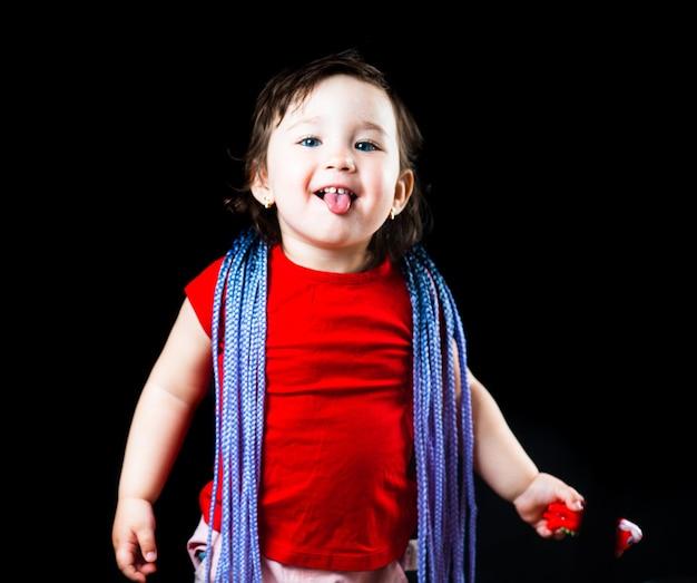 Une petite fille sur fond noir avec des tresses afro, tressées artificielles en bandes élastiques et mise sur mignon