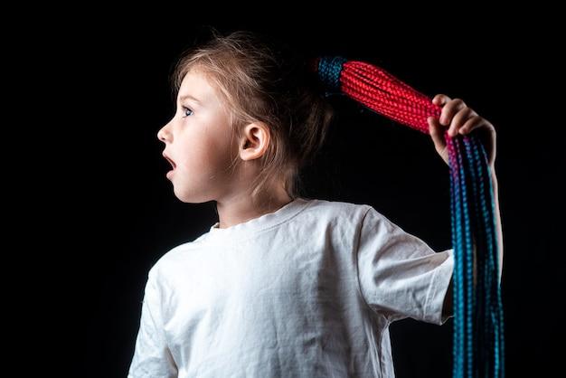 Petite fille sur fond noir avec des tresses afro turquoises et roses attachées en poney...