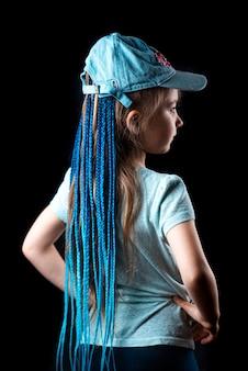 Une petite fille sur fond noir avec des tresses de bandes élastiques afro bleues sur une bande élastique dans un bonnet