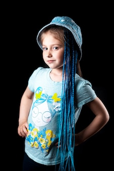 Petite fille sur fond noir avec des tresses de bandes élastiques afro bleues sur une bande élastique dans un chapeau