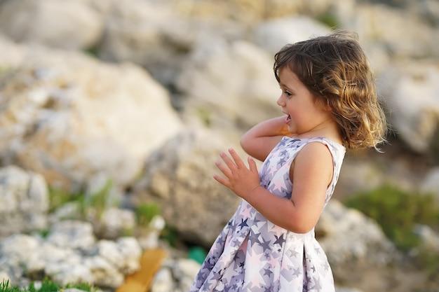 Petite fille sur le fond des rochers méditerranéens