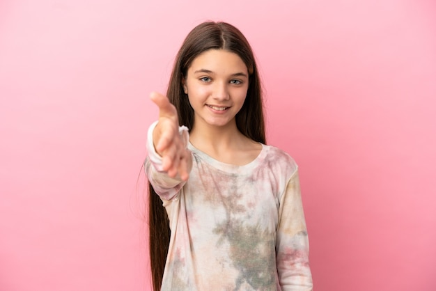 Petite fille sur fond rose isolé se serrant la main pour conclure une bonne affaire