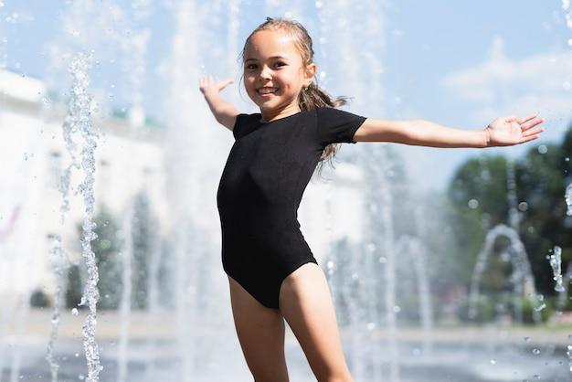 Petite fille avec une fontaine d'eau derrière