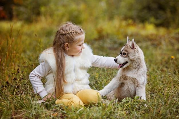 Petite fille frisée est assis dans la forêt d'automne avec des chiots husky