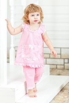 Petite fille frisée vêtue d'une robe rose et pieds nus sortant de la maison et descendant les escaliers